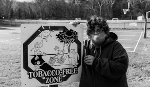 Woman Vaping Next to Tabacco Free Zone Sign
